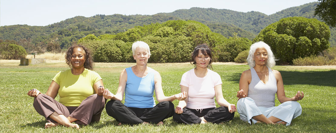 Vier ältere Frauen sitzen im Lotussitz auf einer Wiese und Meditieren