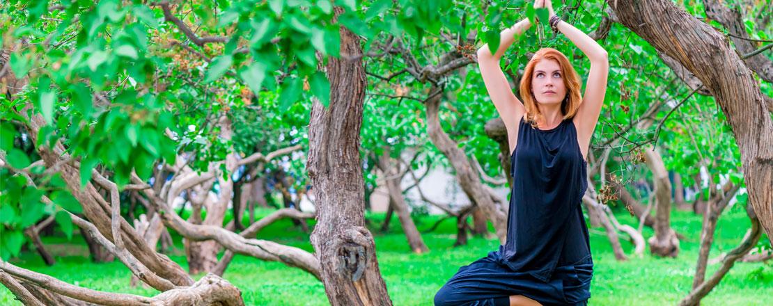 Rothaarige Frau macht zwischen vielen kleineren Bäumen Yoga