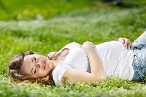 Schwangere Frau liegt glücklich auf einer grünen Wiese