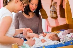 Zwei Frauen wickeln ein Baby