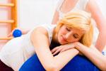 Schwangere Frau entspannt auf einem großen blauen Ball und von einer Heilpraktikerin massiert